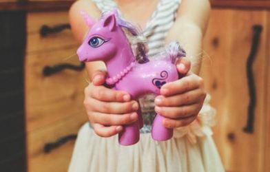 Child holding purple pony toy