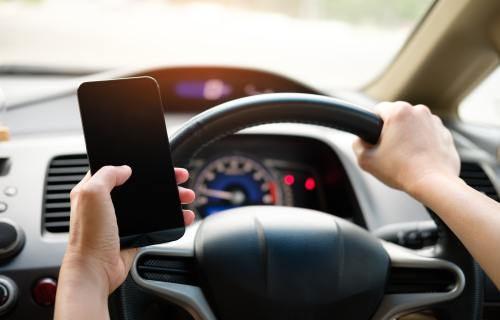 Distracted driving: person using phone behind wheel