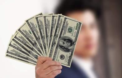 Man holding $100 bills