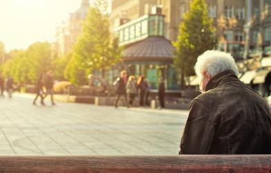 Older, retired person sitting alone on a bench