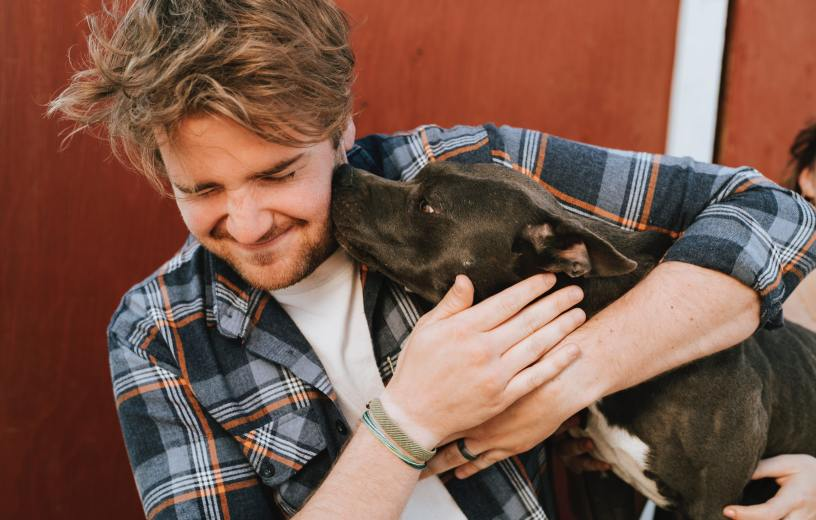 Owner hugging dog that's licking his face