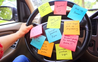 Person with busy to-do list, post-it notes on steering wheel