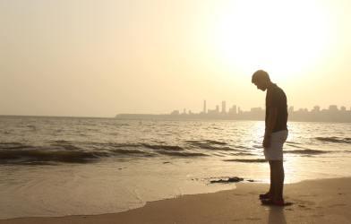 Sad young man at beach alone