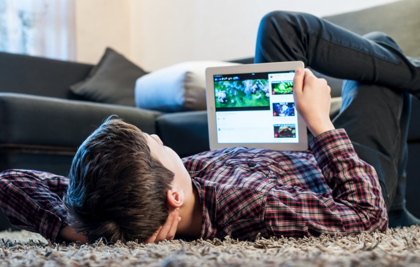 Teenager laying on the floor in the room looking at iPad or tablet