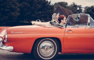 Couple driving in convertible Thunderbird