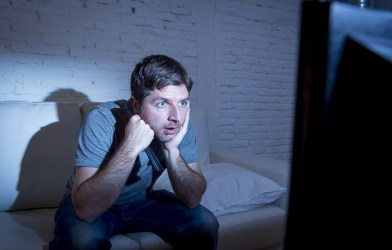 Man sitting on couch watching television