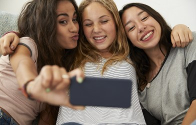 Three teen girls taking selfie at home