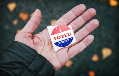 "Election Day voting: Person holding ""I Voted"" sticker"