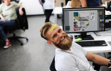 """Office employee with """"Be Happy"""" sticker on his head while sitting at desk"""
