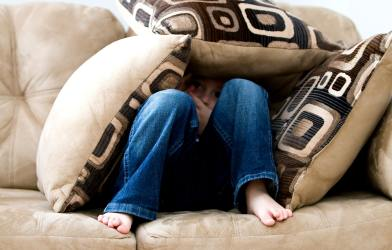 Child hiding on the couch