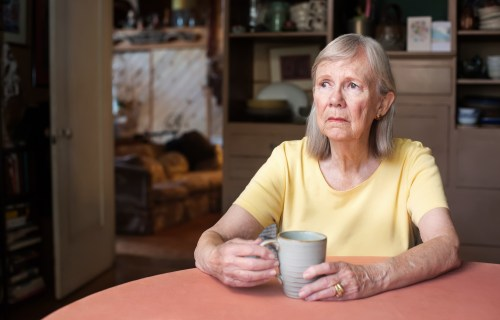 Sad, older woman sitting at table