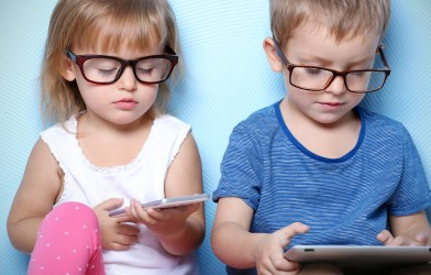 Young children wearing glasses while looking at smartphone, tablet screens