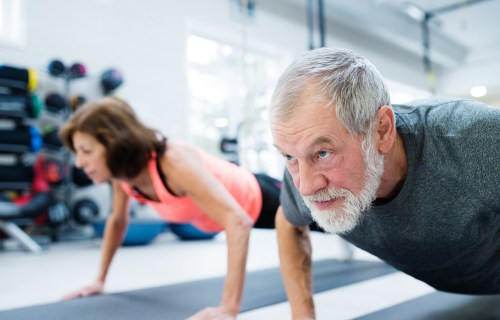 Older adults working out in the gym doing pushups