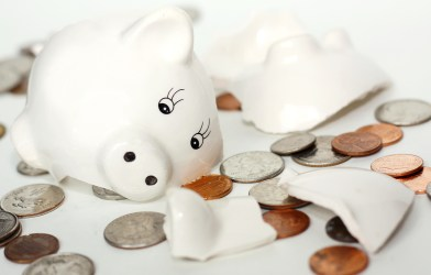 Raided retirement account: Broken piggy bank surrounded by money