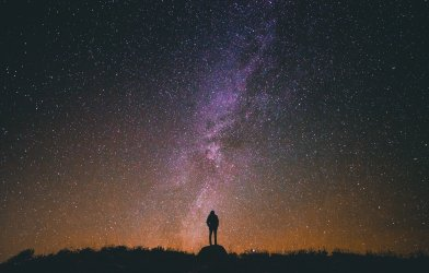 Person looking up at outer space, night sky