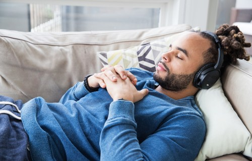 Man napping on the couch while listening to music