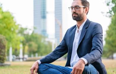 Man practicing meditation in city park