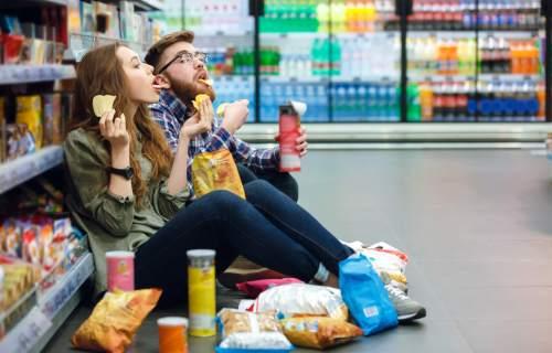 Couple sitting on supermarket floor eating chips, snacks