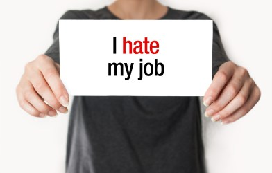 "Woman holding ""I Hate My Job"" sign"