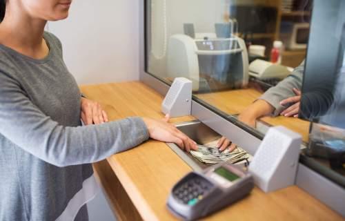 Woman making withdrawal of cash at local bank
