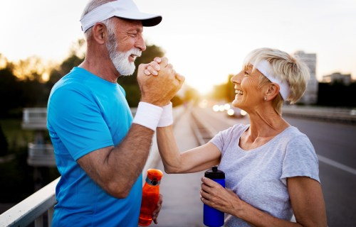 Happy older senior couple exercising or working out
