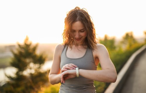 Woman walking checking pedometer for step count