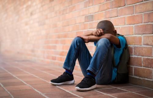 Sad black student alone in hallway at school