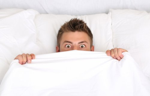Scared man in bed having bad dream or nightmare