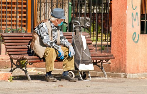 Man sitting on bench with mask, gloves during coronavirus / COVID-19 outbreak