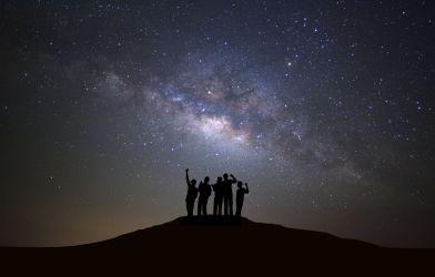 People looking up at Milky Way galaxy in night sky