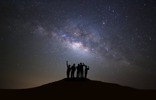People looking up at Milky Way galaxy in night sky