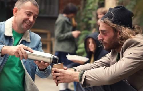 Man volunteering to feed homeless man