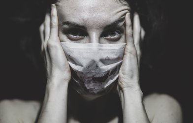 Woman in mask stressed during COVID-19 / coronavirus pandemic