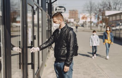 Man wearing face mask while entering store during COVID-19 / coronavirus outbreak