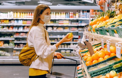 Woman in face mask at grocery store during coronavirus outbreak