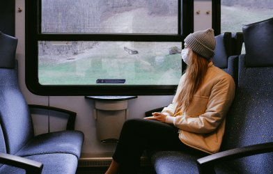 Woman on train wearing mask during coronavirus / covid-19 outbreak