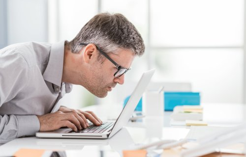Man battling vision problems, macular degeneration effects while looking at computer