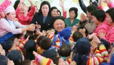 Kim looks like a teddy bear, really, among the children of the orphanage.