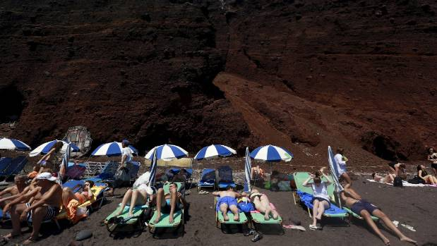 Tourists sunbathe on the Red Beach on the Greek island of Santorini.