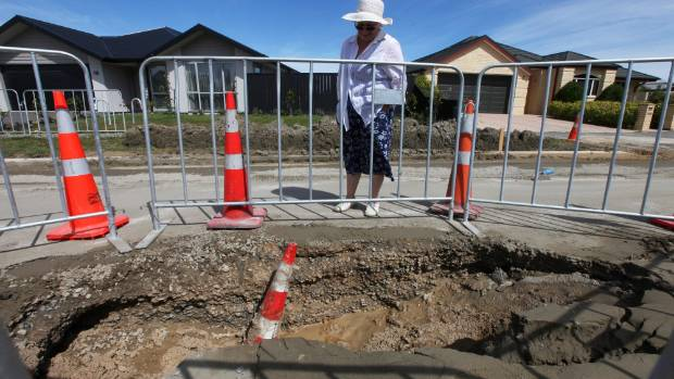 Parklands resident Jill Hurley assesses a sink hole that opened up on Bower Ave in Sunday's 5.7 magnitude earthquake.