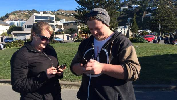Candice Bresser and Calvin Baverstock catching 'em all at the Pokemon Go hotspot in Sumner, Christchurch.