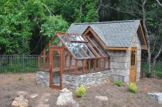 This Tudor greenhouse is attached to the house at the gable end and has a stone base providing thermal mass