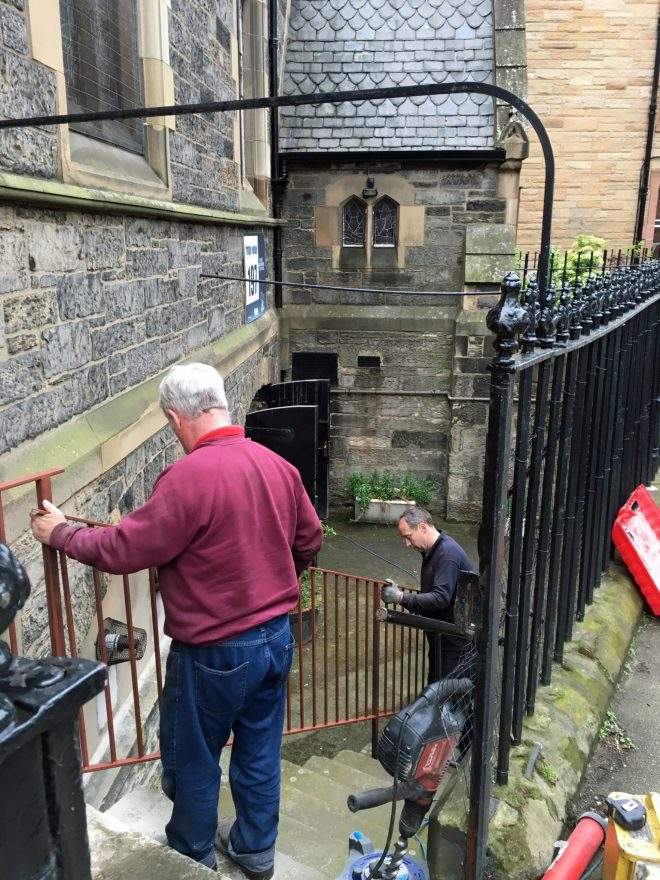 A new railing is fitted to the steps to the undercroft at St Vincent's by father and son Graeme Brodie, blacksmiths. There had been no railing previously.