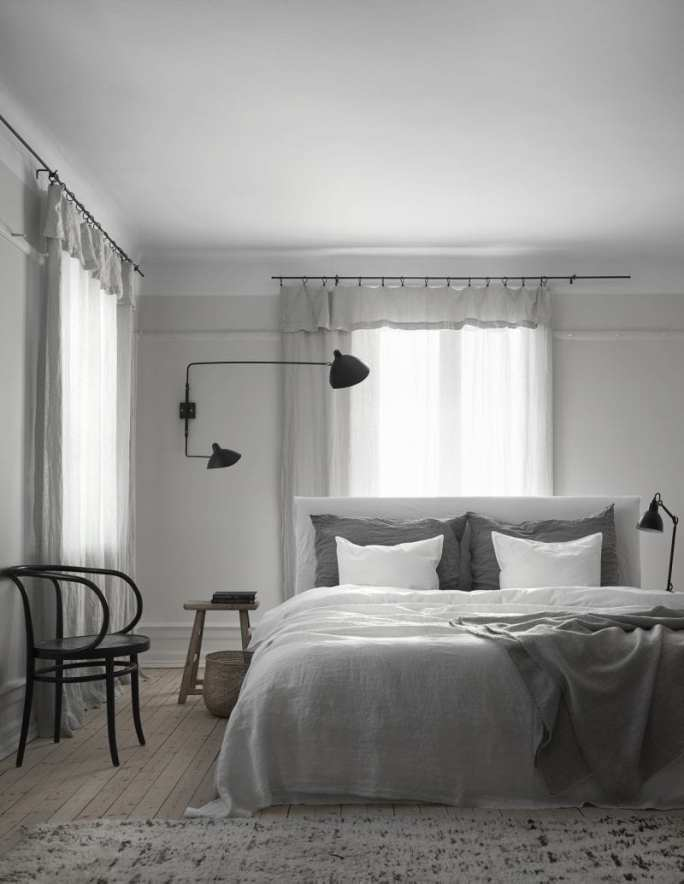 Bedroom with grey linen, bent wood armchair, black wall lamps | Home of Artilleriet's Owners