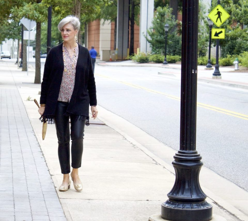 enjoying sweater weather in faux leather leggings, silk blouse and fring cardigan by style at a certain age