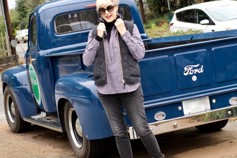 beth from style at a certain age wears high rise skinny jeans, tissue turtleneck, gingham shirt jacket, and puffer vest
