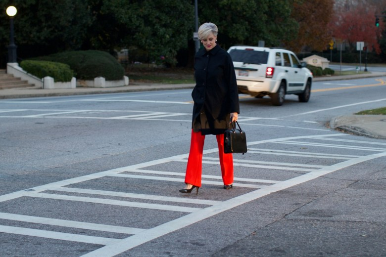 beth from Style at a Certain Age wears Anthropologie red pants, pink and red shirt, Everlane black raincoat, and black suede pumps