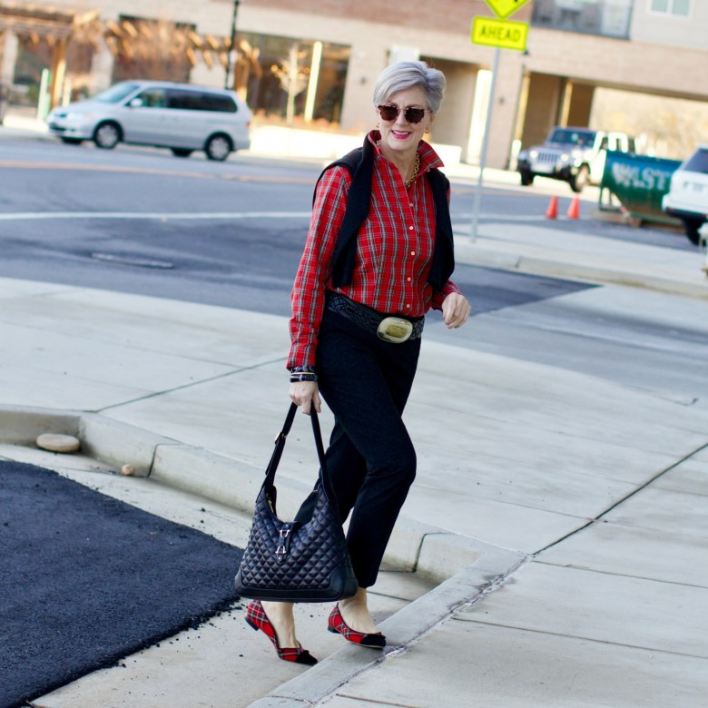 beth from Style at a Certain Age wears a tartan plaid shirt, black cropped ankle pants, tartan plaid flats, military coat and quilted hobo handbag.