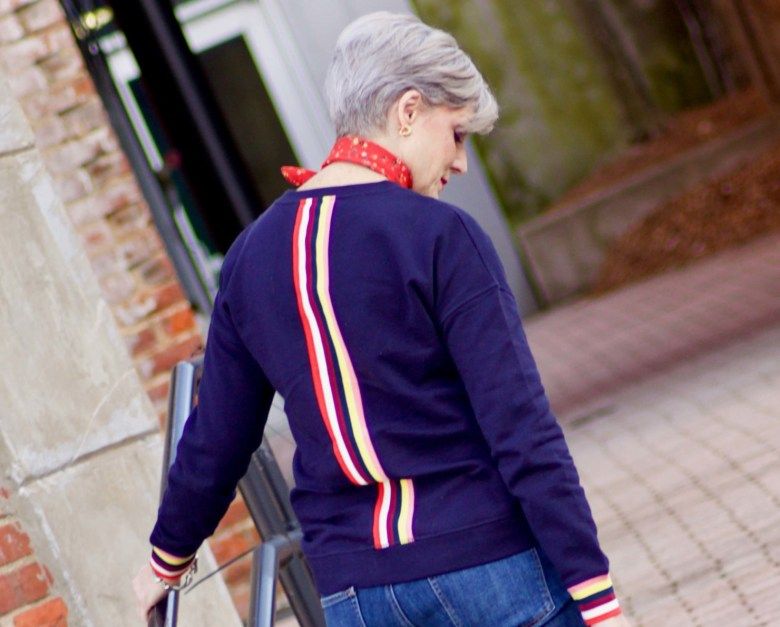 beth from Style at a Certain Age wears a navy blue sweatshirt, blue jeans, Everlane loafers and a J.Crew scarf