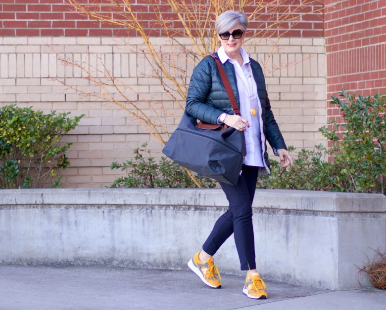 beth from Style at a Certain Age wears Athleta pants, white shirt, puffer jacket, and sneakers